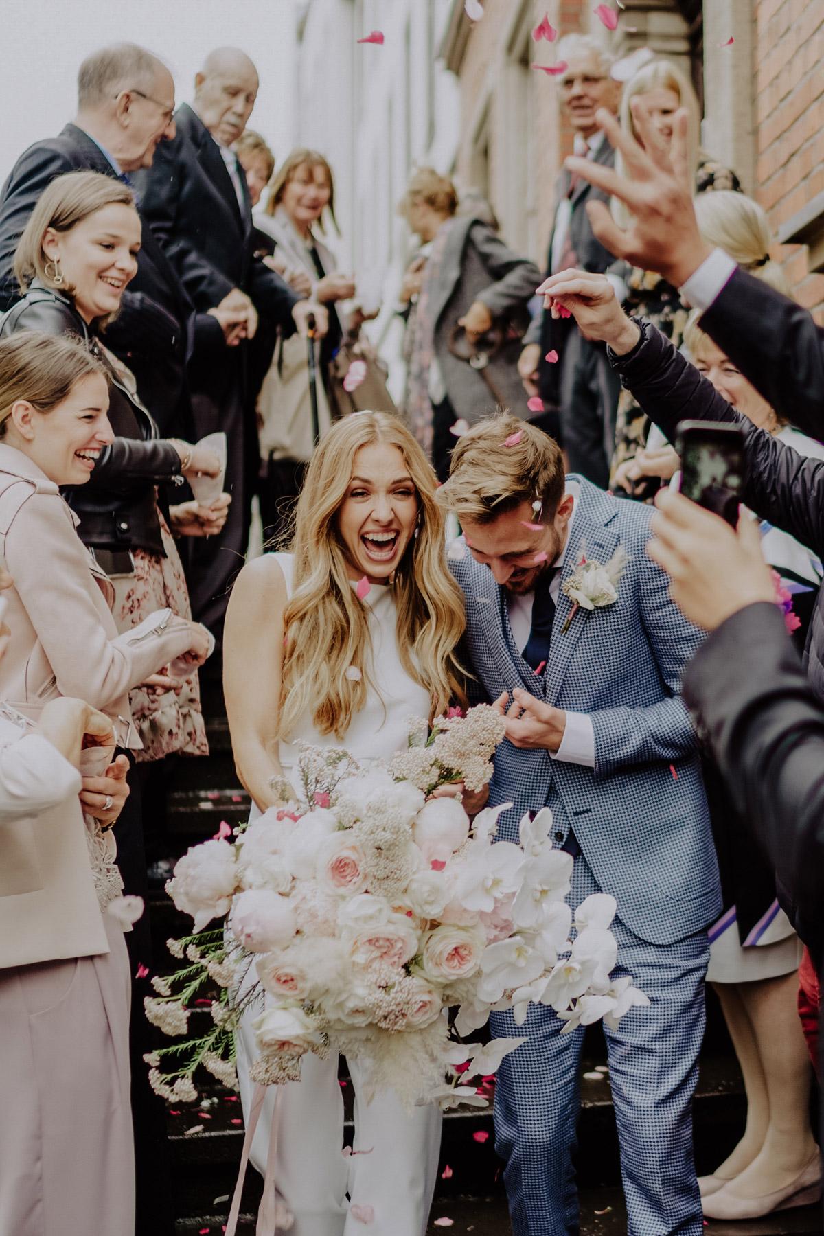 Standesamt Hochzeit Foto Ideen Gäste werfen Blütenblätter auf Hochzeitspar; frisch verheiratetes glückliches Ehepaar bei standesamtlicher Hochzeit mit Regen von Hochzeitsfotografin Berlin © www.hochzeitslicht.de #hochzeitslicht