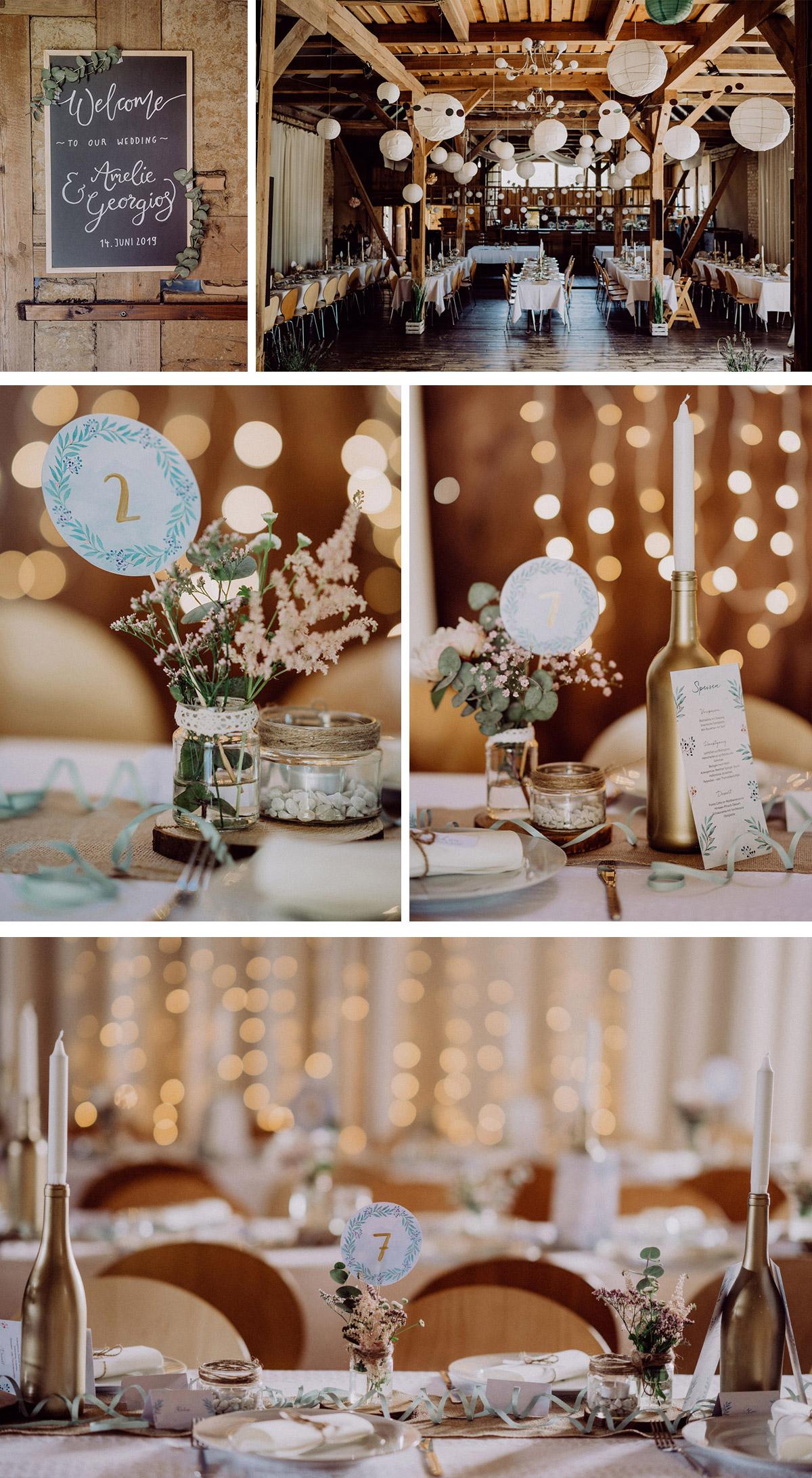 Scheunenhochzeit Dekoration vintage, Beleuchtung mit Lichterketten und DIY goldene Flaschen als Kerzenhalter, Tischdeko mit handgemalten Platznummern in DIY Gläsern mit Hochzeitsblumen auf Holzscheiben, Scheune Deko Willkommen auf Tafel, beiger Tischläufer, weiße Lampions von Decke