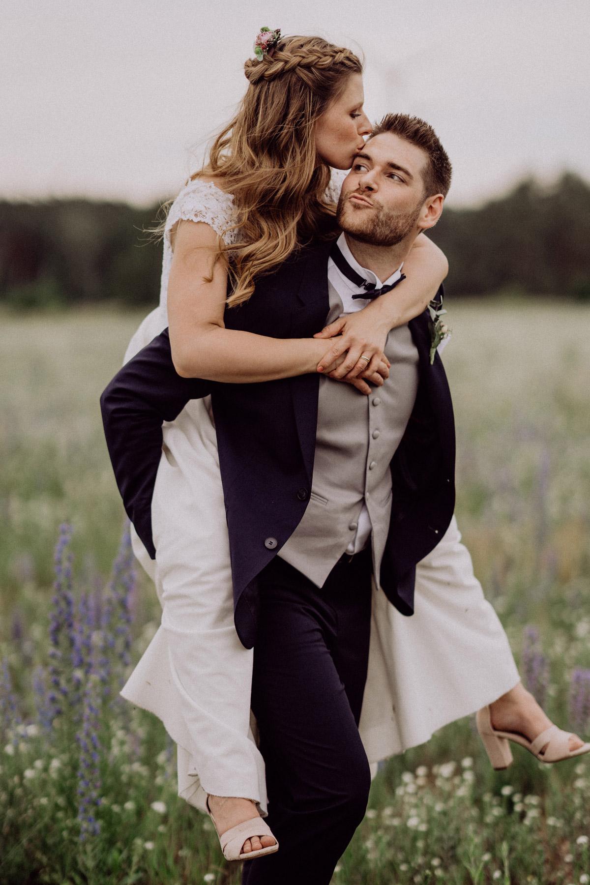 Hochzeit Paarshooting Natur Bräutigam trägt Braut auf Blumenwiese und sie versuchen sich zu küssen