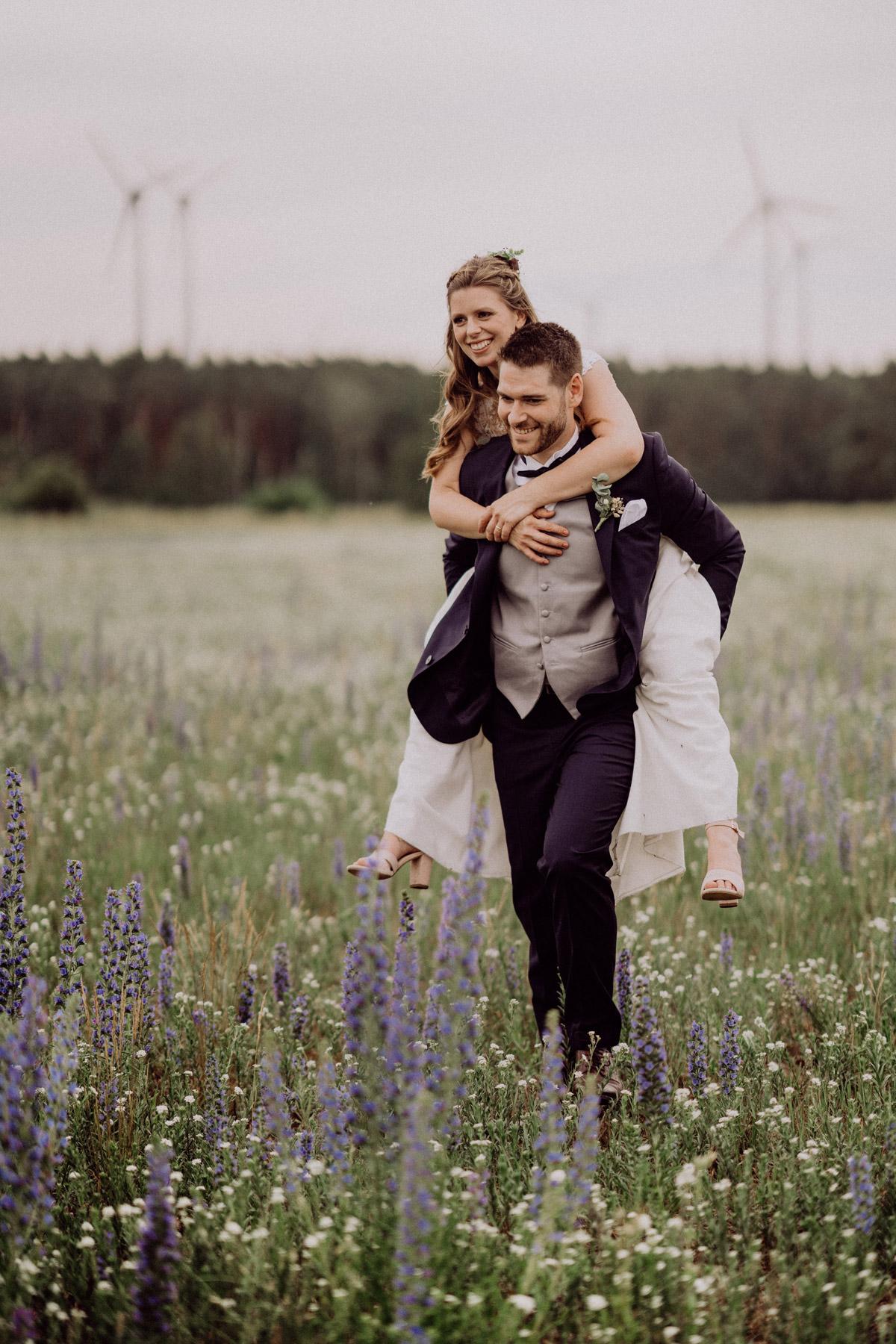 Fotos Hochzeit Ideen, Inspiration Brautpaar im Huckepack läuft über Feld