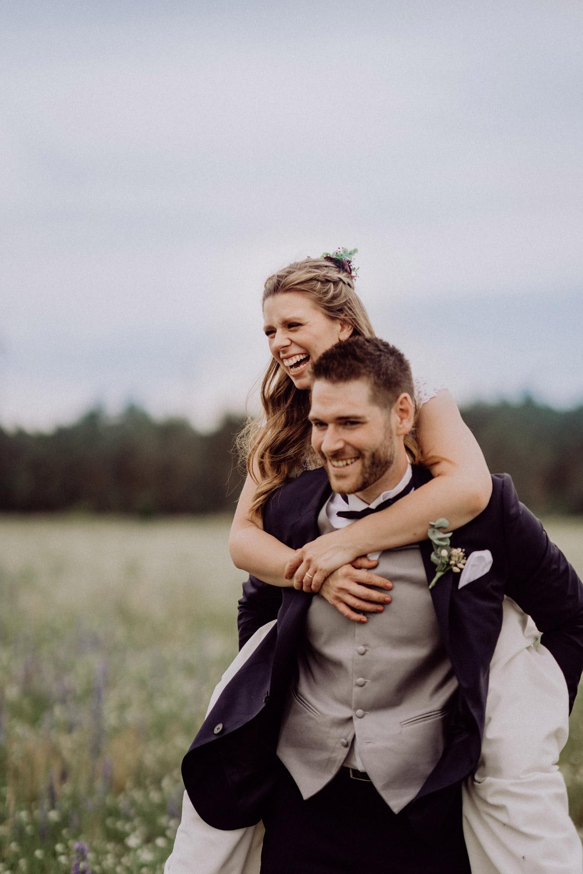 Hochzeitsbilder Ideen, Paarfotosmit glücklich lachendem Brautpaar, Bräutigam trägt Braut auf Rücken über Feld