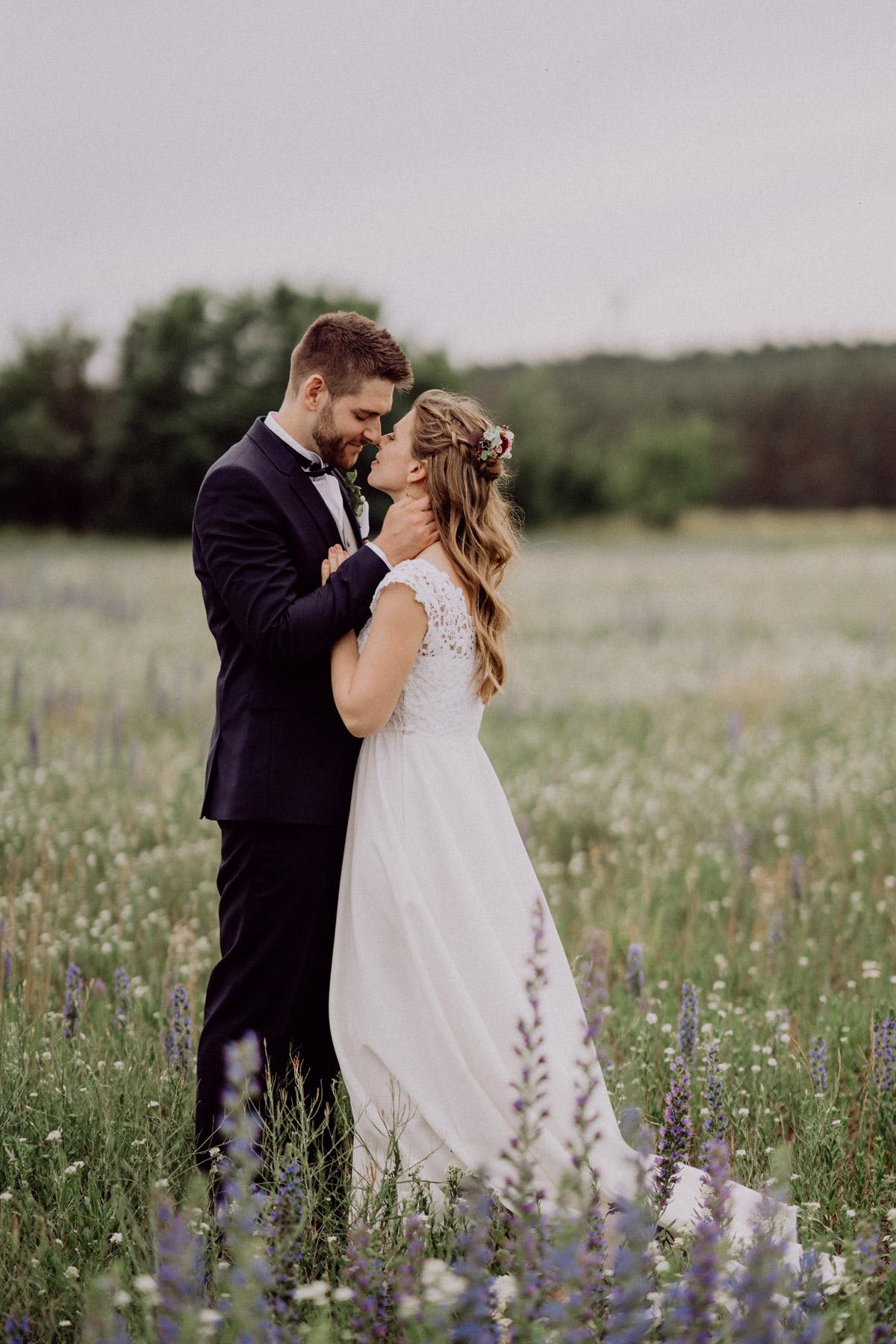Hochzeit Bilder in Natur, Paarshooting auf Wiese mit Wildblumen, Brautpaar steht Nase an Nase und kuschelt miteinander ganzer Körper ist zu sehen