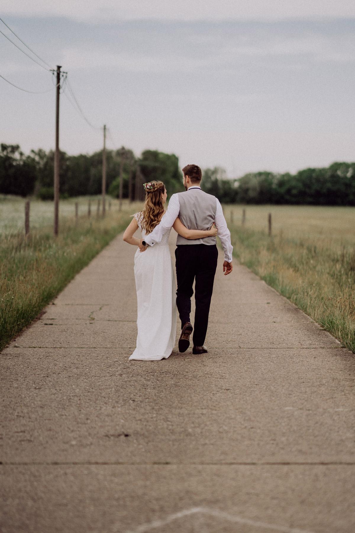 Hochzeitsfotos Ideen, Brautpaar von hinten läuft Arm in Arm auf Weg
