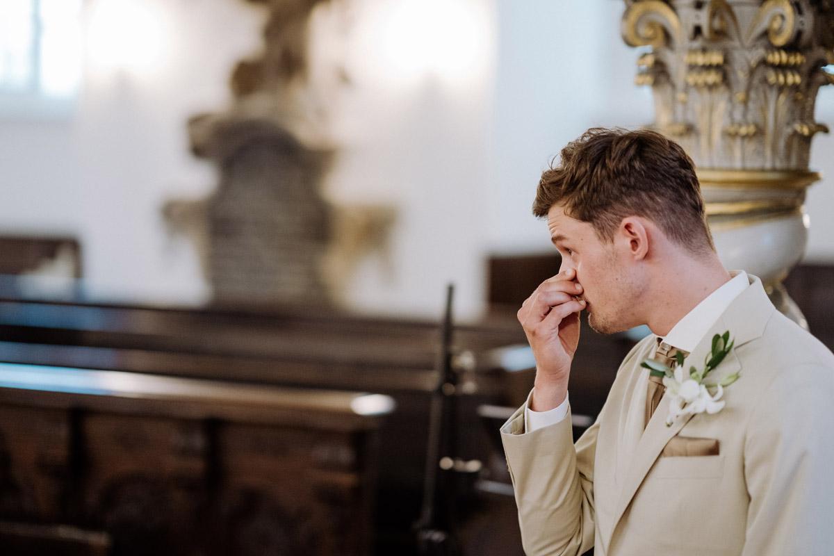 First Look Trauung Kirche Bräutigam am Altar - Diese intime Hotel Hochzeit Berlin mit kirchlicher Trauung Berlin vermittelt durch die stilvolle Hochzeitslocation sowohl das Gefühl, entspannt die Hochzeit zu Hause zu feiern, als auch in einer Suite im Luxushotel Waldorf Astoria zu heiraten. Mehr Hochzeit Deko Fotos von der kleinen, eleganten #hochzeit oder #tinywedding mit wenig Gästen und Trauung Kirche im Blog von Hochzeitsfotografin und Hochzeitsfilmer aus Berlin #hochzeitslicht © www.hochzeitslicht.de