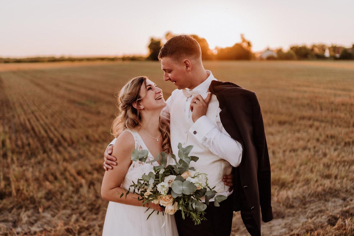 Fotoshooting Brautpaar nach standesamtlicher Hochzeit bei Sonnenuntergang auf Feld - natürliche Hochzeitsfotos Standesamt auf Schloss Kartzow von Hochzeitsfotograf Berlin © www.hochzeitslicht.de #hochzeitslicht