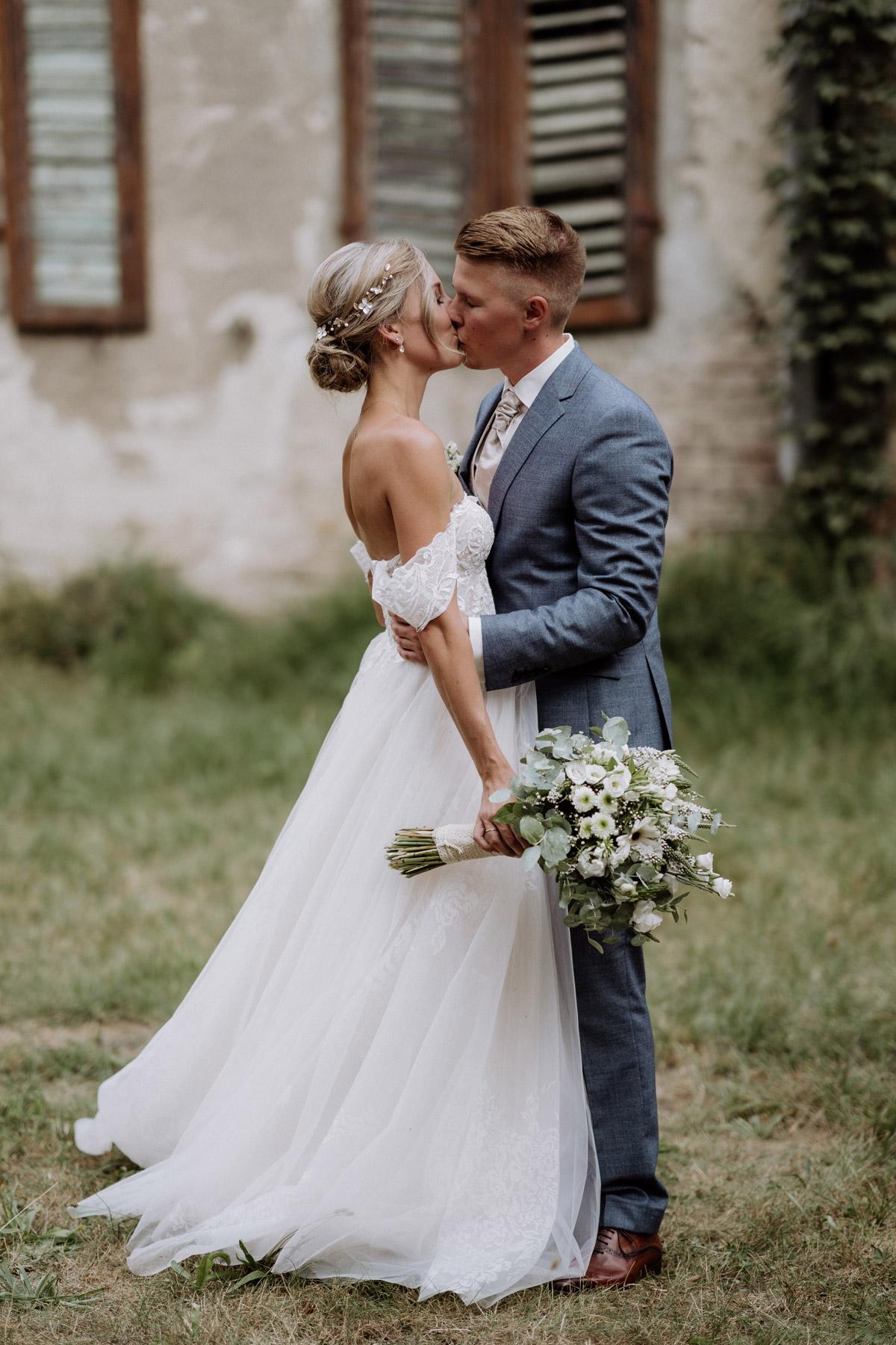 Brautpaar Hochzeit Shooting Idee Braut und Bräutigam küssen sich in Ganzkörper Aufnahme von vintage Hochzeitsfotograf Berlin, weißer Brautstrauß mit Eukalyptus © www.hochzeitslicht.de #hochzeitslicht #hochzeit #brautpaarfoto #idee #hochzeitsshooting