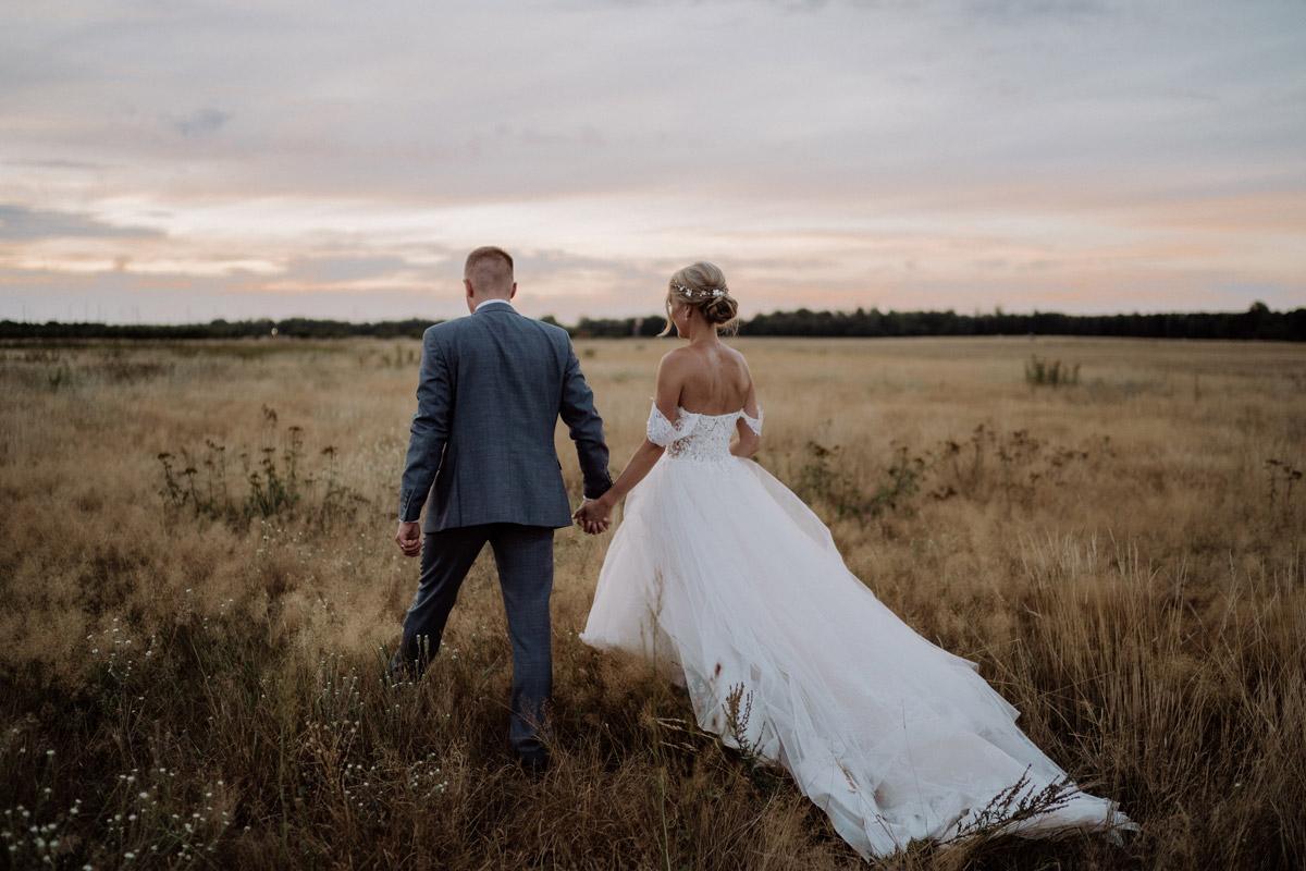 Fotoshooting Braut und Bräutigam laufen bei Sonnenuntergang auf Feld - Hochzeit Shooting Ideen von vintage Hochzeitsfotograf Berlin © www.hochzeitslicht.de #hochzeitslicht auf Schloss Kartzow