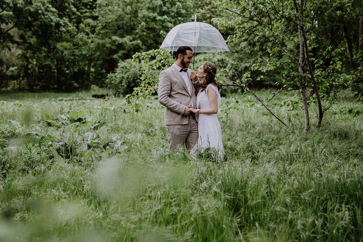 Fotoshooting Brautpaar Regenhochzeit transparenter Regenschirm - Standesamtliche Hochzeit in Berlin Neukölln bei Regen von Hochzeitsfotograf Berlin © www.hochzeitslicht.de #hochzeitslicht