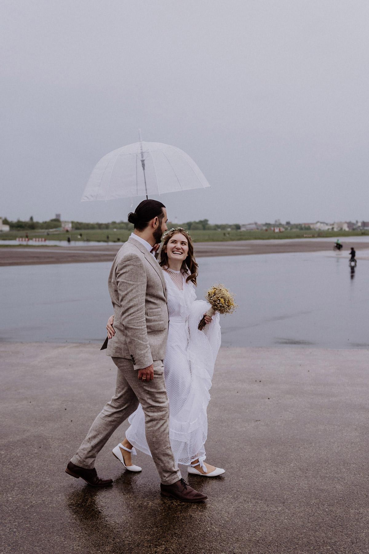 Hochzeit mit Regen Hochzeitspaar mit Regeschirm nach standesamtlicher Trauung in Berlin, © www.hochzeitslicht.de Hochzeitsreportage Berlin #hochzeitslicht #hochzeitfoto #standesamt #regenschirm