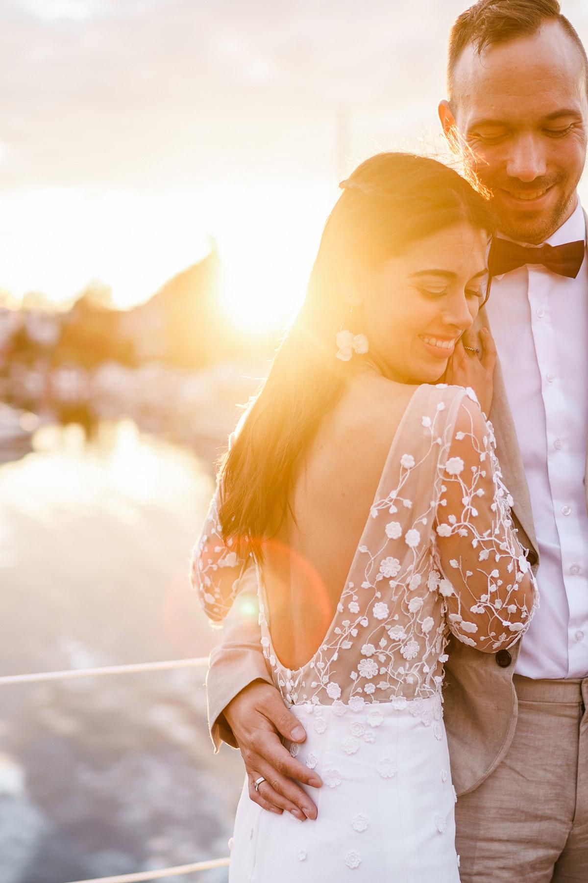 Brautshooting im Sonnenuntergang mit Hochzeitskleid von Zo & Willow Berlin: figurbetontes Brautkleid mit seitlichem Schlitz mit Oberteil aus Spitze mit langen Ärmeln und tiefem, runden Rückenausschnitt; Brautfrisur offene Haare halb geflochten mit einzelnen Strähnen, die Gesicht umspielen; natürliches Braut-Make-up #Brautportrait #Brautposing #weddingdress #realbride #echtebraut - Corona Hochzeit Berlin auf dem Wasser in Spree Hausboot von Hochzeitsfotograf Berlin © www.hochzeitslicht.de #hochzeitslicht