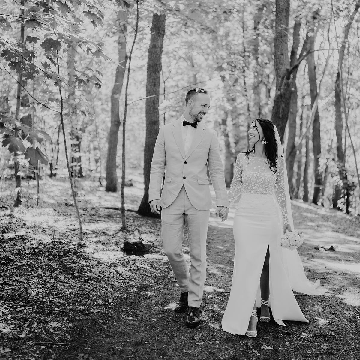 Schwarz Weiß Hochzeitsfoto im Wald: Brautpaar im Gehen trägt modernes Outfit; Brautkleid mit Schlitz in Seite- Corona Hochzeit Berlin auf dem Wasser in Spree Hausboot von Hochzeitsfotograf Berlin © www.hochzeitslicht.de #hochzeitslicht