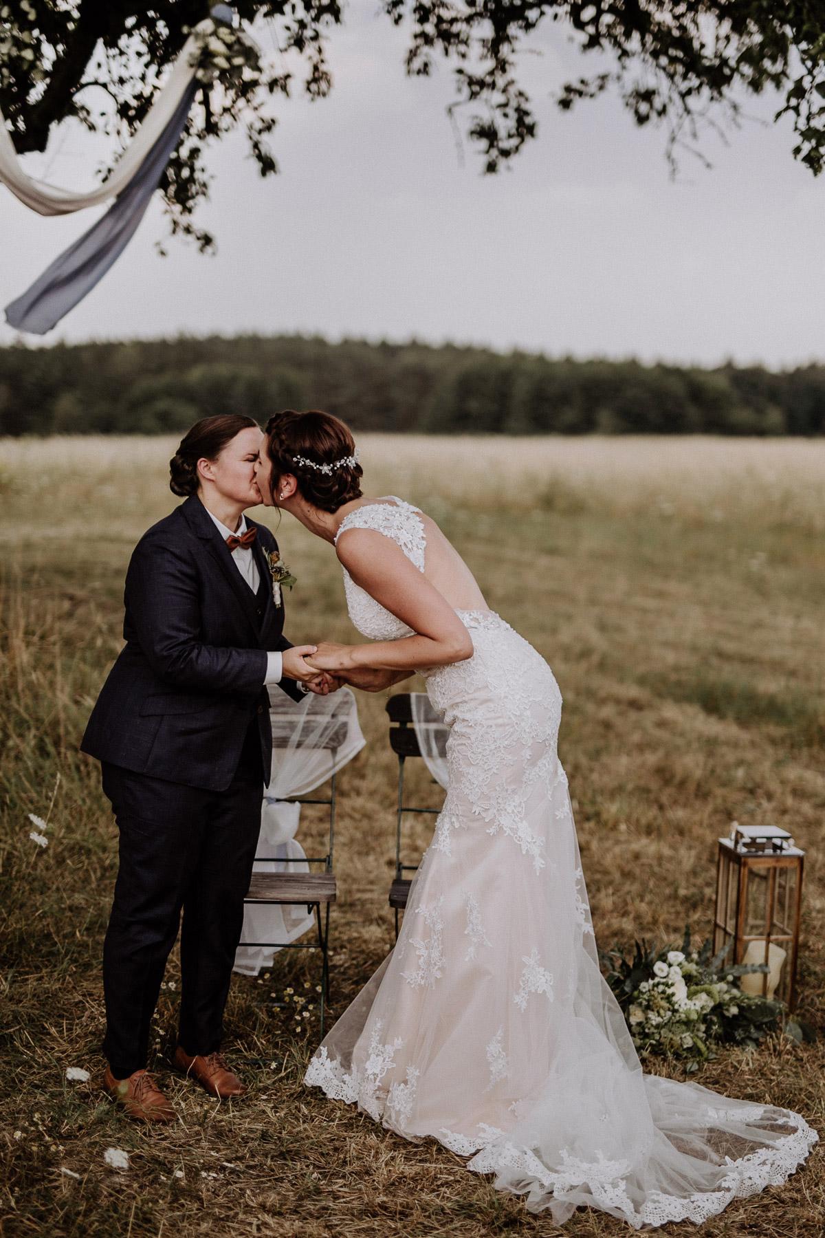 Lesbische Corona Hochzeit: Kuss freie Trauung auf Feld in Nähe Hochzeitslocation Gut Sarnow in Brandenburg von Hochzeitsfotograf Berlin © www.hochzeitslicht.de #hochzeitslicht #gaywedding #samesexwedding