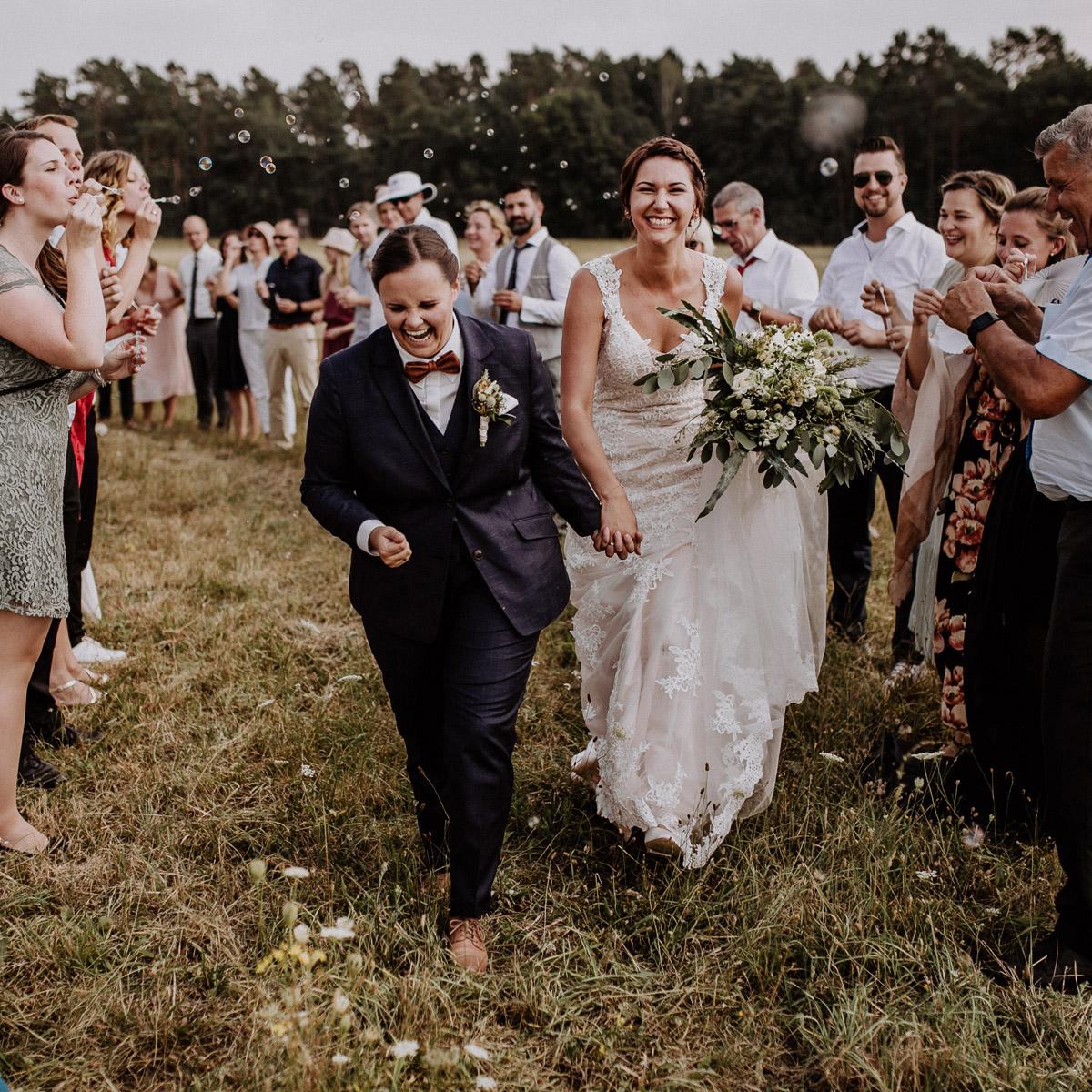 Gleichgeschlechtliche Hochzeit Frauen: zwei Bräute beim Auszug nach Trauung auf Feld in Nähe Hochzeitslocation Gut Sarnow in Brandenburg von Hochzeitsfotograf Berlin © www.hochzeitslicht.de #hochzeitslicht