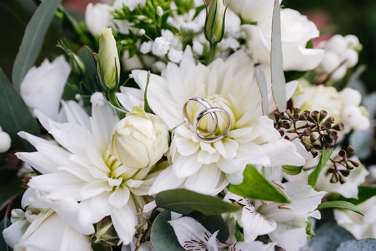 weiße Hochzeitsblumen: Brautstrauß weiß grün mit Eheringen in silber, weiße Rosen, Dahlien, Schneebeeren und blaugrüner Eukalyptus, grüne Olivenzweige; Oberhafenkantine Berlin © www.hochzeitslicht.de #hochzeitslicht