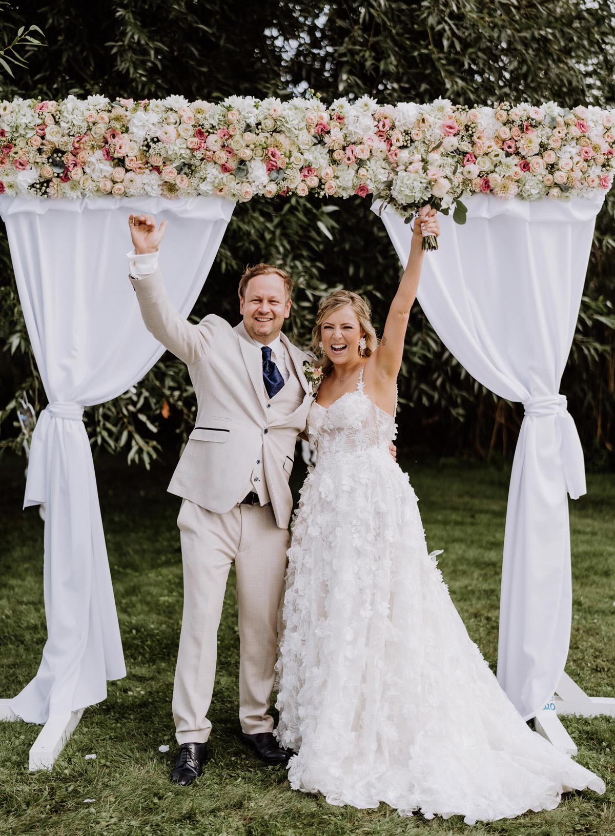 Boho Hochzeitspaar reißt glücklich nach ihrer freien Trauung die Arme nach oben. Die #hochzeitslicht Braut trägt ein Galia Lahav Traumkleid. - Hochzeitsfoto von Hochzeitsfotograf Potsdam im Resort Schwielowsee © www.hochzeitslicht.de
