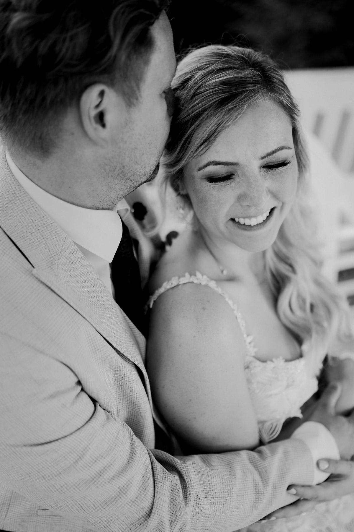 Boho Braut wird von Bräutigam umarmt: Glücklich lächelnde Braut auf ihrer Corona-Gartenhochzeit am Wasser in den Armen ihres Bräutigams. Hochzeitsfotograf Potsdam aus Berlin © www.hochzeitslicht.de #hochzeitslicht