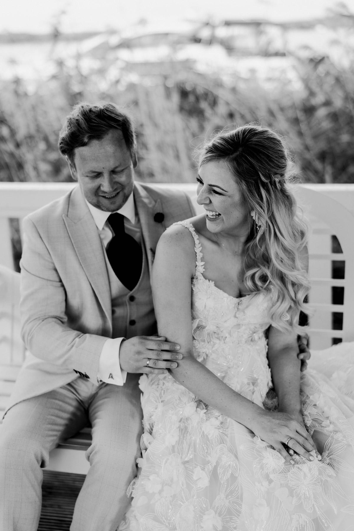 Boho Hochzeitspaar lacht glücklich: Brautpaarshooting Idee für authentische und emotionale Hochzeitsfotos. Wir lieben diesen Moment von der freien Trauung in der Hochzeitslocation Resort am Schwielowsee am Wasser in Brandenburg. © www.hochzeitslicht.de #hochzeitslicht