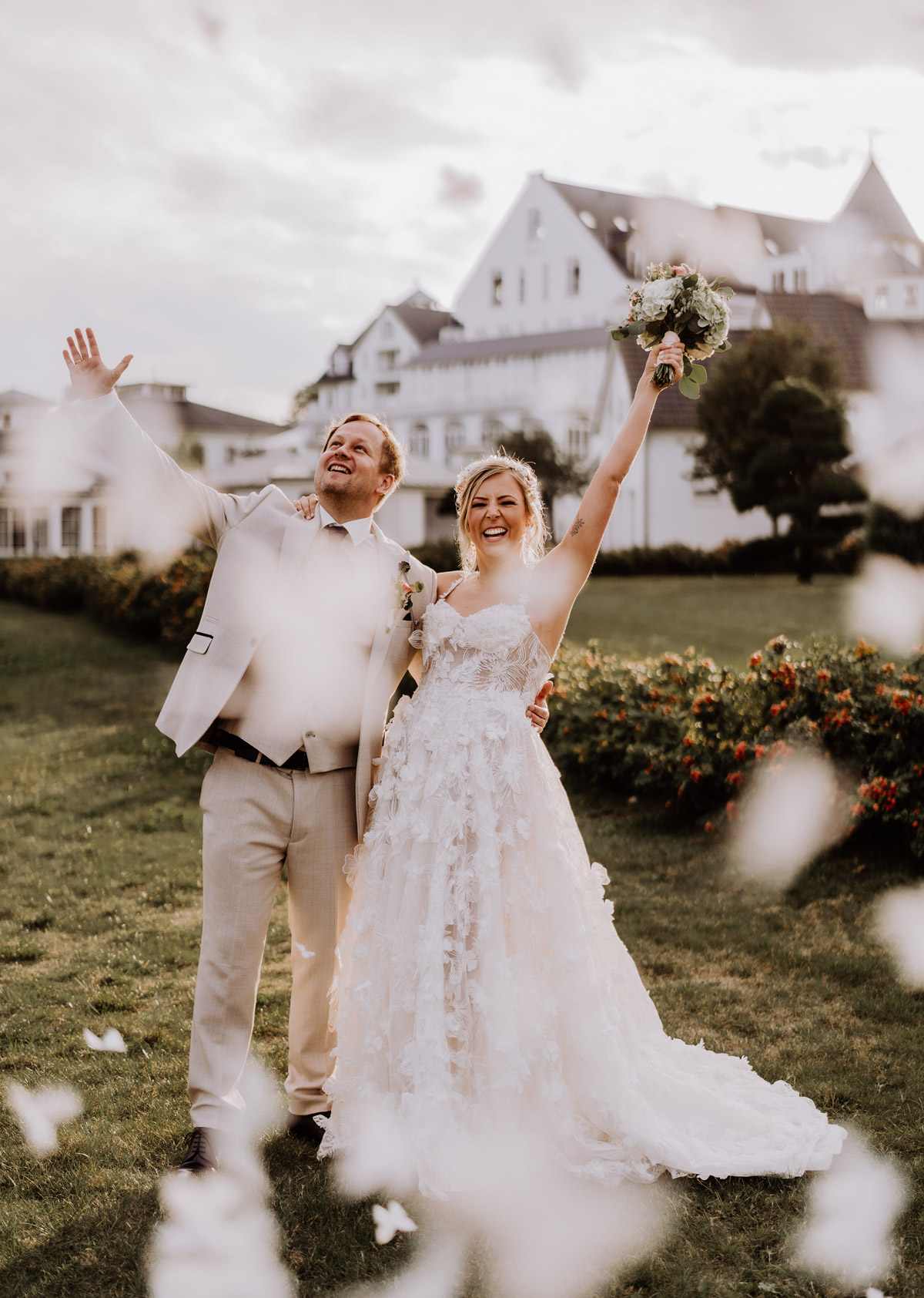 glückliches boho Hochzeitspaar: Fotoshooting Idee Brautpaar mit weißem Schmetterlingskonfetti für Ehepaar in hellem Hochzeitsoutfit auf Corona Gartenhochzeit am Wasser in Brandenburg. © www.hochzeitslicht.de #hochzeitslicht