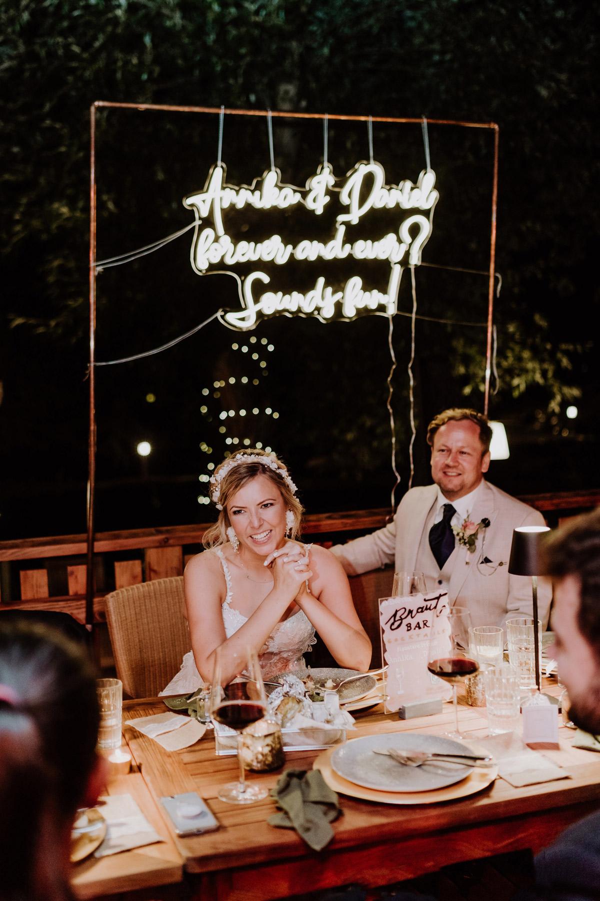 Hochzeitdeko Idee Hochzeitsspruch leuchtet: Boho Hochzeitspaar sitzt vor ihrem kurzen Hochzeitsspruch. Annika & Daniel forever and ever? Sounds fun! Hochzeitsreportage aus Berlin von © www.hochzeitslicht.de #hochzeitslicht