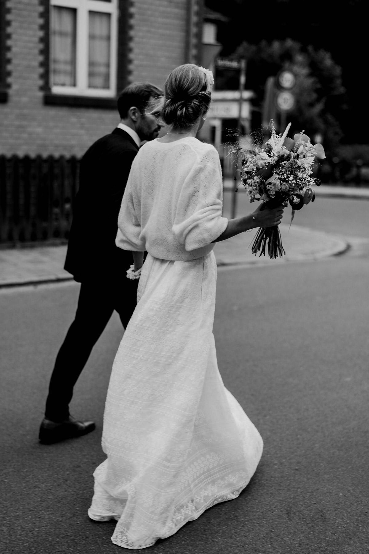 Hochzeitspaar von hinten geht auf Straße: Die Braut trägt einen wärmenden Pullover zum Hochzeitskleid. Nach der Standesamt Hochzeit ging das Brautpaar durch das Dorf zur Hochzeitslocation. Hochzeitsmoment von Spreewald Hochzeitsfotograf aus Berlin © www.hochzeitslicht.de #hochzeitslicht