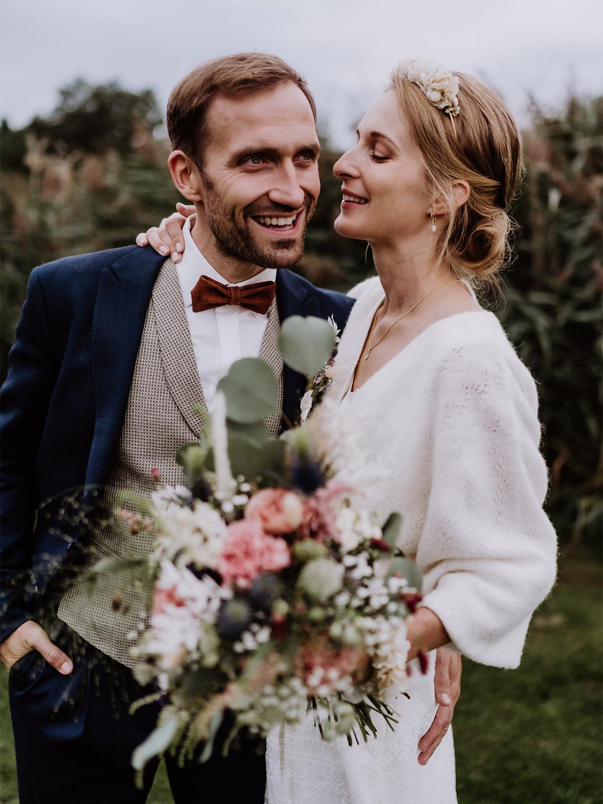 Hochzeitsoutfit Brautpaar im Herbst zum Standesamt: Die Braut trägt einen Haarreif und einen langen Pullover zu ihrem zweiteiligen Kleid. Der Bräutigam trägt eine braune Fliege zum dunkelblauen Hochzeitsanzug und der hellen Weste. © www.hochzeitslicht.de #hochzeitslicht