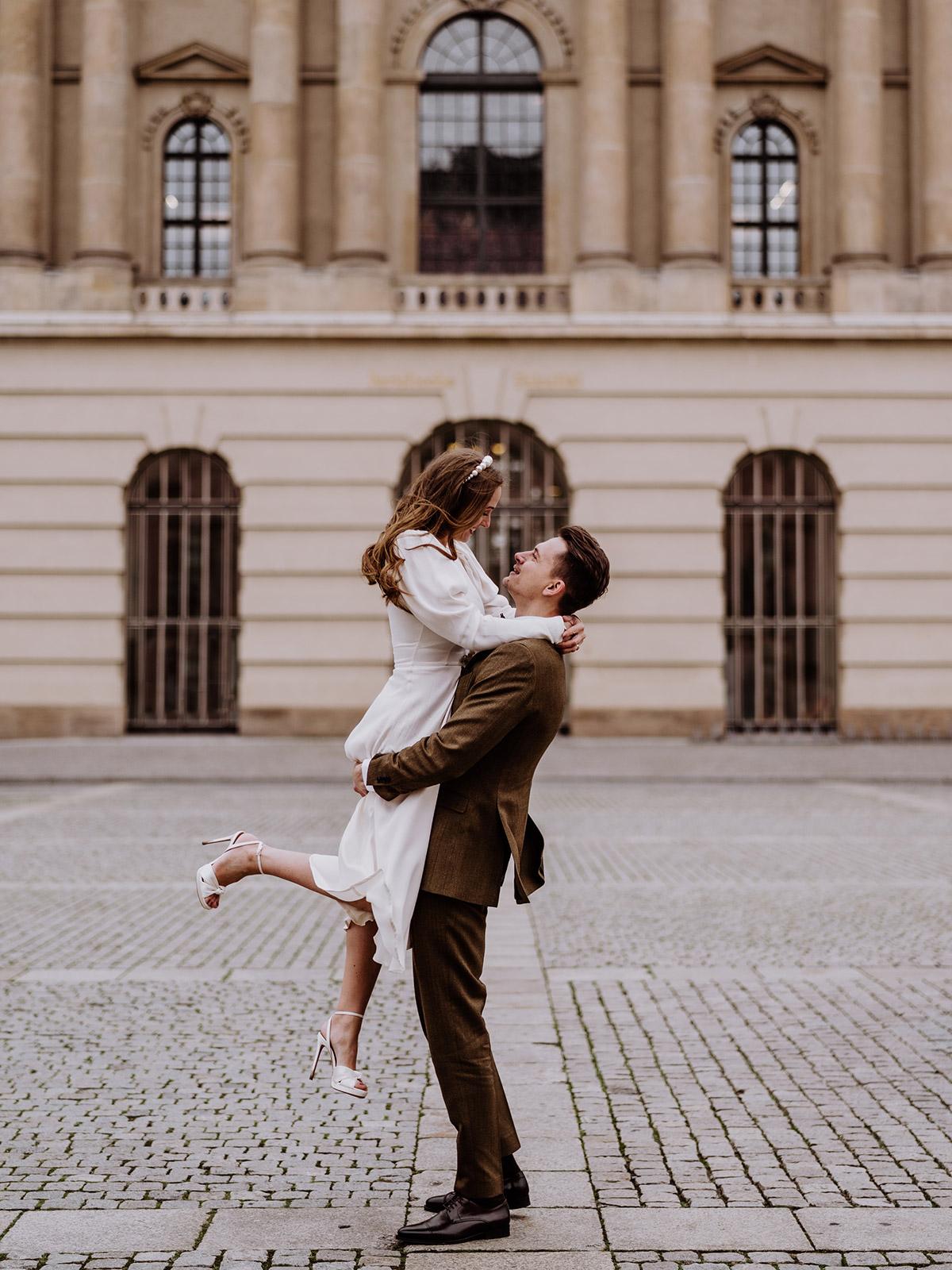 Brautpaar Fotoshooting Idee: Hochzeitsfoto nach der standesamtlichen Hochzeit im Winter. Bräutigam hebt Braut an, die Hochzeitskleid mit langen Ärmeln trägt. Mehr zur Elopement Winterhochzeit während Corana im Blog © www.hochzeitslicht.de #hochzeitslicht