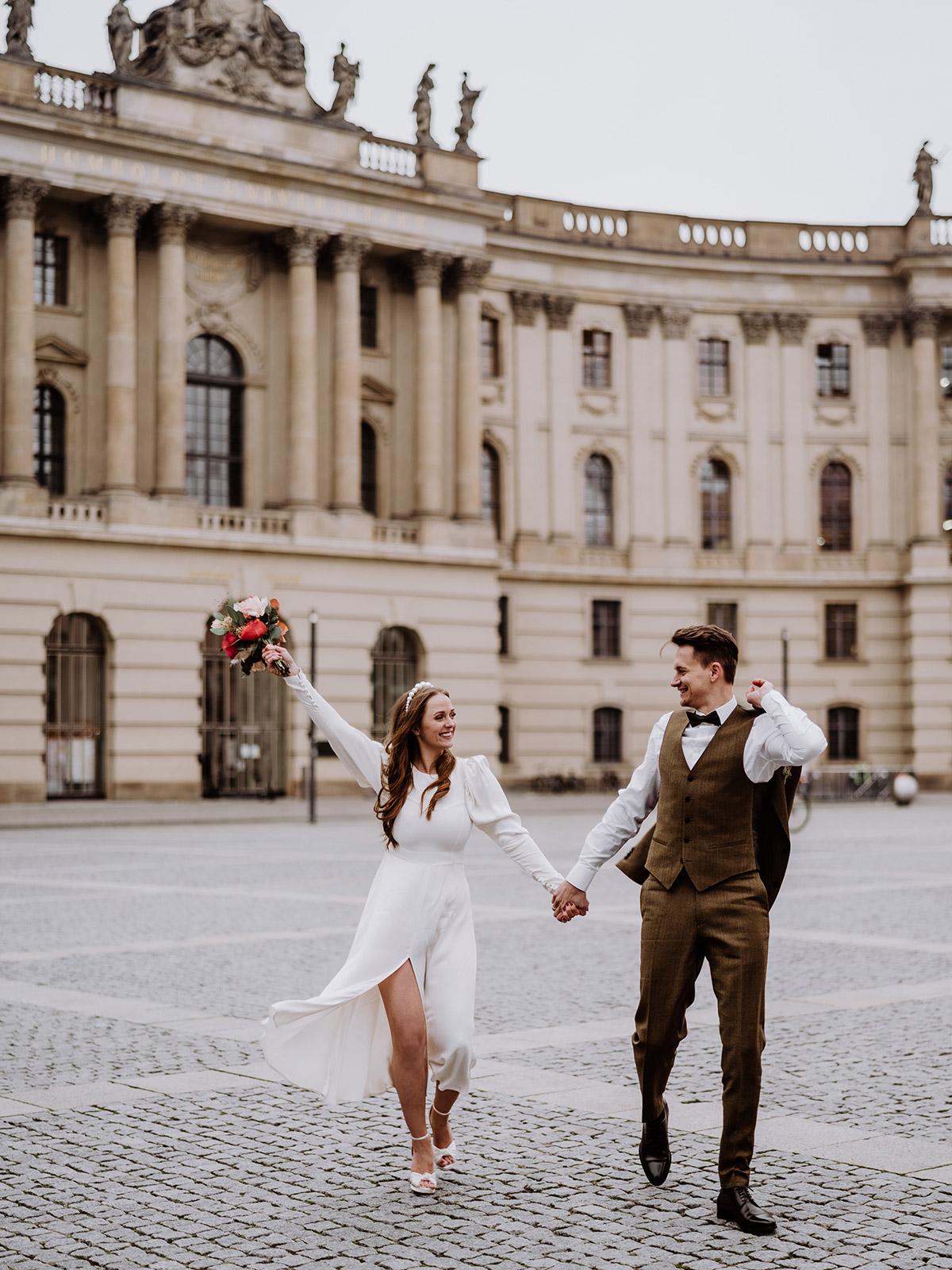 Hochzeitsfotografin hält jubelndes Hochzeitspaar auf Bebelplatz mitten in Berlin fest. Das Winter Hochzeitsoutfit der Braut bestand aus einem langärmligen Brautkleid mit Puffärmeln und Schlitz an der Seite. © www.hochzeitslicht.de #hochzeitslicht
