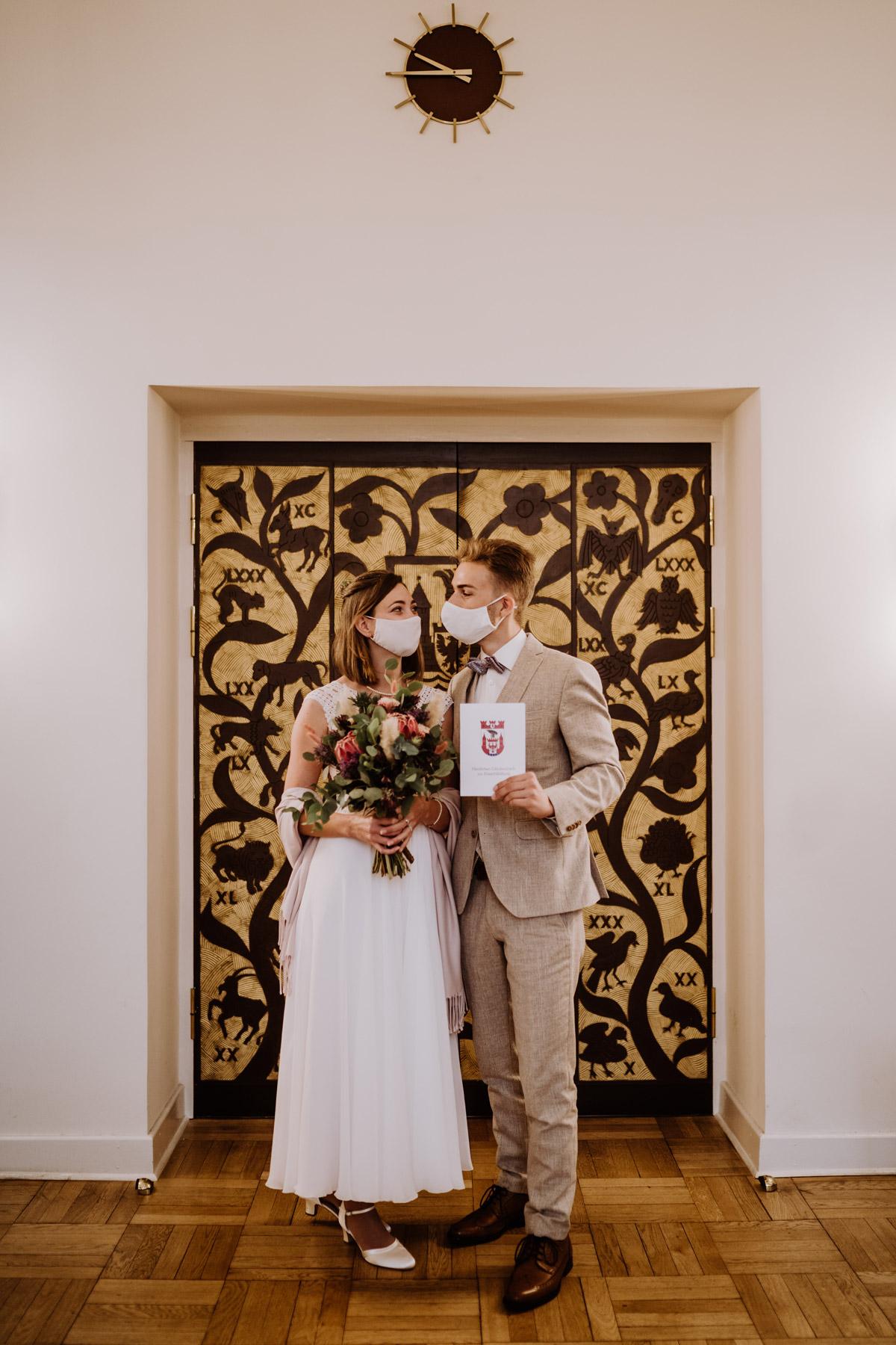 Standesamt Spandau Berlin: Das Brautpaar heiratet standesamtlich in der Corona Pandemie in einem Elopement allein zu zweit. Der Hochzeitsfotograf hat das Standesamtfoto trotz Hochzeitspaar mit Covid-19 Masken direkt nach der Trauung erstellt. © www.hochzeitslicht.de #hochzeitslicht