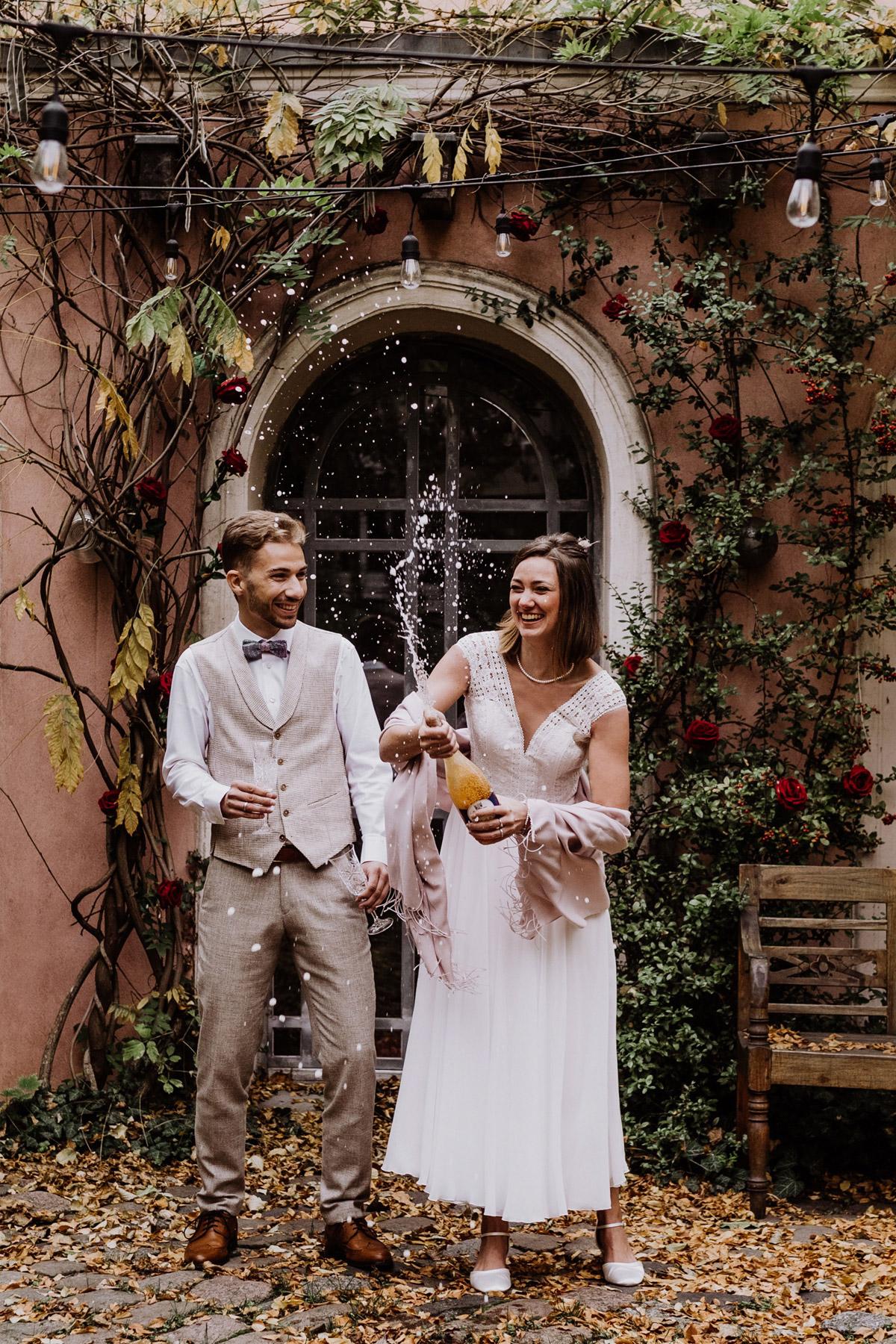 Standesamt Fotograf Berlin: Idee für das Hochzeitsshooting direkt nach der standesamtlichen Trauung im Winter. Das vintage Hochzeitspaar schüttelt eine Champagnerflasche und spritzt damit ausgefallen und kreativ für ihre Hochzeitsfotos. Mehr im Blog von © www.hochzeitslicht.de #hochzeitslicht